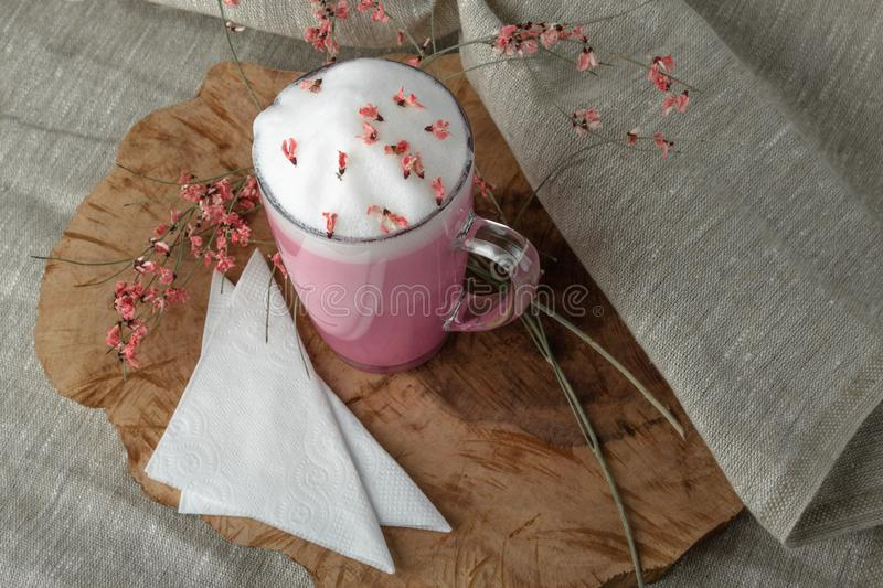 Pink coffee latte macchiato in a glass cup on a wooden backing decorated with dried flower stock image