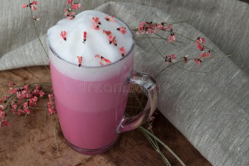 Pink coffee latte macchiato in a glass cup on a wooden backing decorated with dried flower royalty free stock photography