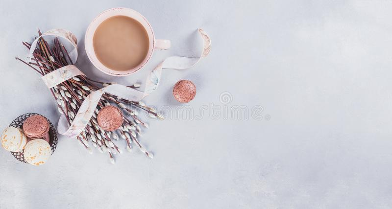 Pink coffee mug with sweet pastel french macaroons and wil royalty free stock images