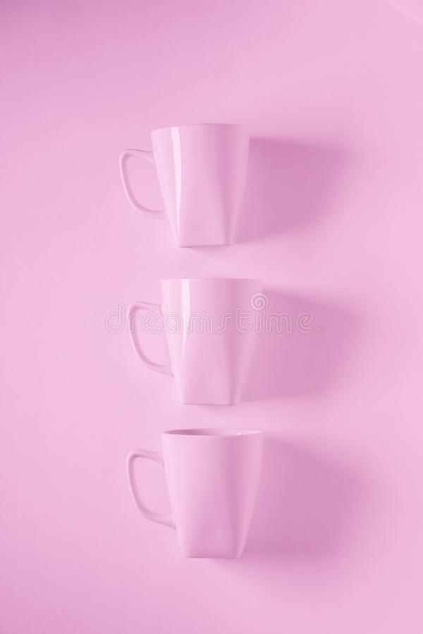 3 pink coffee mugs on pink background in a vertical row with empty copyspace. 3 monochromatic pink coffee mugs lined up in a row on pink background with blank stock photos