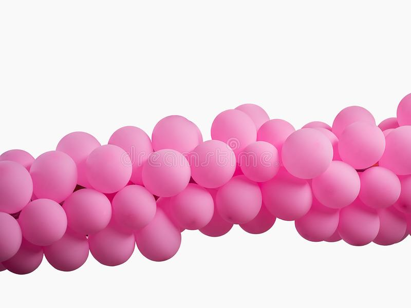 Pink color decorated balloons in a row over white background stock photos