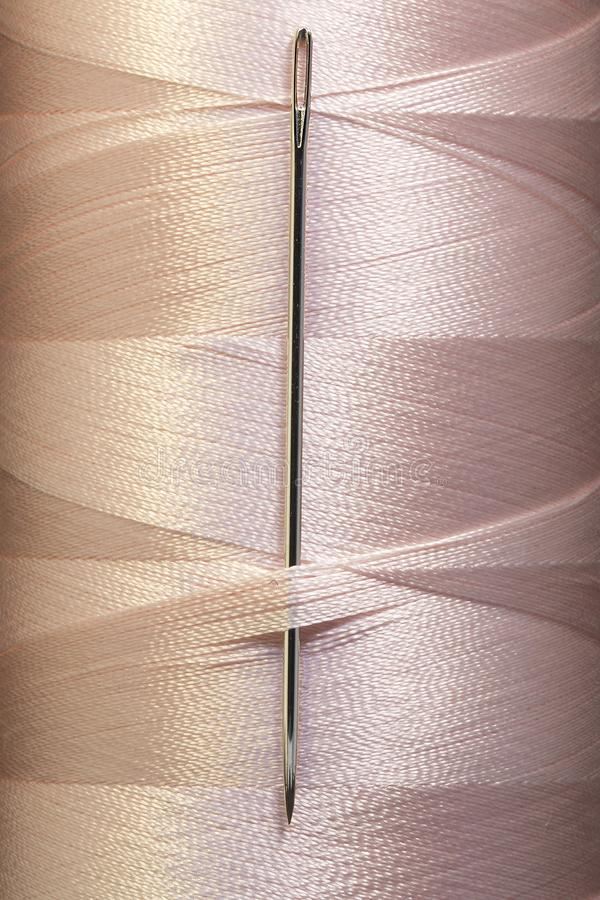 Pink color threads in spool with sewing needle, macro royalty free stock photography
