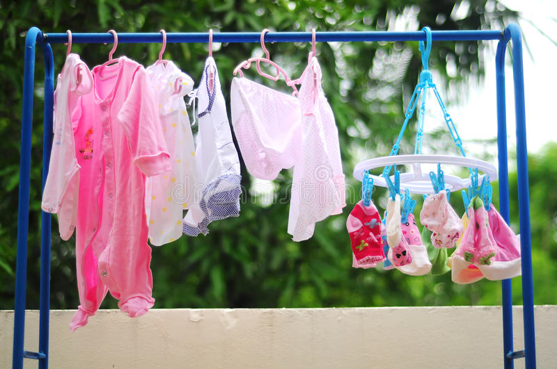 Pink and colored baby laundry hanging on a clothesline royalty free stock photo
