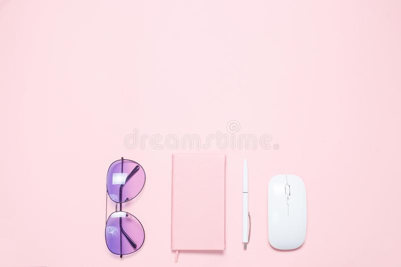 Pink colored desk with pink colored diary, white pen, white mouse and purple sunglasses. Minimalistic flat lay. Composition with copy space for bloggers royalty free stock image