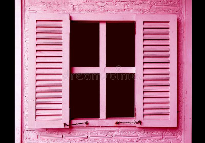 Pink colored window shutters on the pink brick wall. Texture background, architecture, art, artistic, beautiful, black, building, closed, colorful, concept stock image