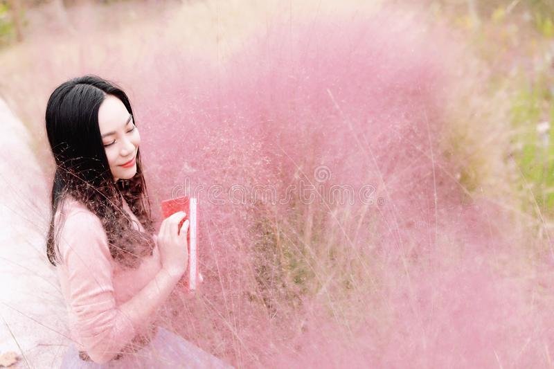 Pretty beautiful cute Asian Chinese woman girl reading book in a flower field outdoor in summer autumn fall park dreamlike garden royalty free stock photo
