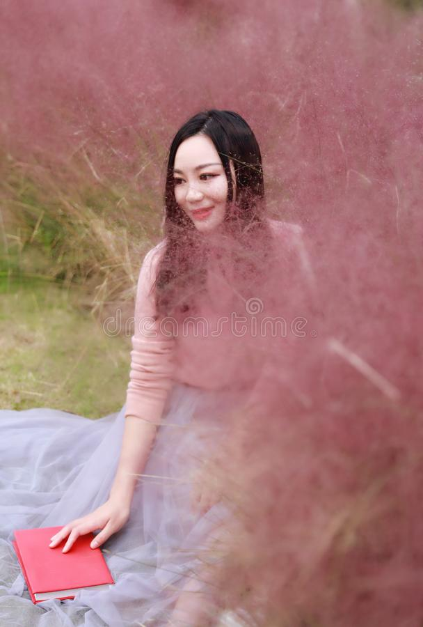Pretty beautiful cute Asian Chinese woman girl reading book in a flower field outdoor in summer autumn fall park grass lawn garden stock photo