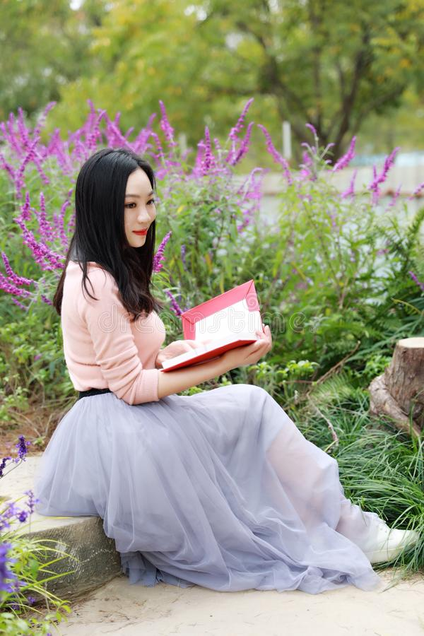 Happy Asian Chinese woman girl dream sit pray flower field autumn fall park lawn hope nature read book knowledge freedom carefree. Pink colour grass lawn, rose stock images