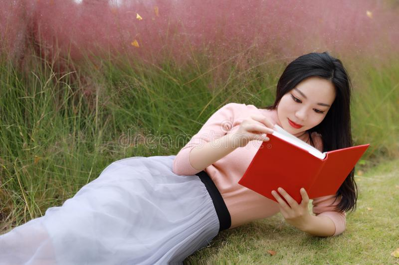 Happy Asian Chinese woman girl lying on grass dream pray flower field autumn fall park lawn hope nature read book knowledge stock photo