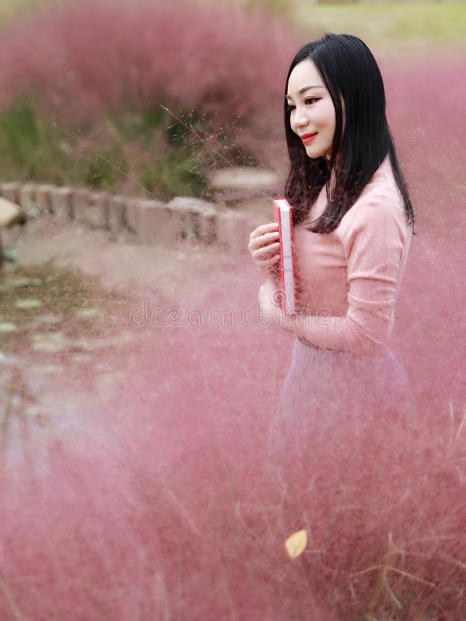 Beautiful Asian Chinese woman girl stand in grass dream pray flower field autumn fall park lawn hope nature read book knowledge stock photos