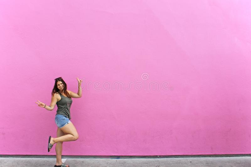 Pink wall and a happy girl. Pink coloured wall seems to be sweet like a candy. Poseing girl standing on one of her legs with a big smile in front of that pink royalty free stock photos