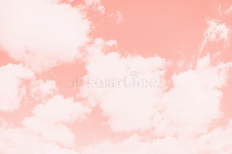 Pink coral color sky background with white clouds. Coral gradient background stock photography