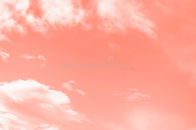 Pink coral color sky background with white clouds. Coral gradient background royalty free stock photography