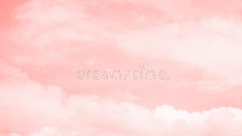 Pink coral color sky background with white clouds. 16:9 panoramic format. Coral gradient background royalty free stock images
