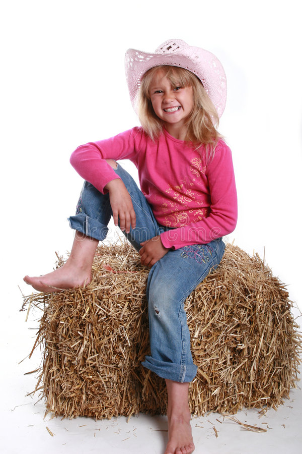 Pink cowboy hat on a girl. Smiling girl wearing a pink cowboy hat stock photo