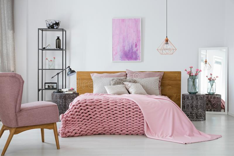 Pink woolen blanket and duvet on warm king size bed in classy bedroom interior, abstract painting on empty wall. Pink cozy woolen blanket and duvet on warm king royalty free stock photo