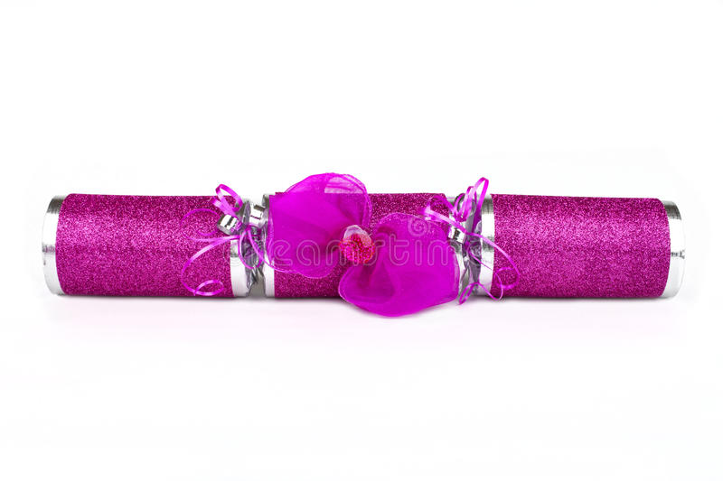 Pink Cracker. A studio shot of a Cracker or otherwise known as a Bon Bon. A traditional cracker consists of a cardboard tube wrapped in a brightly decorated royalty free stock image