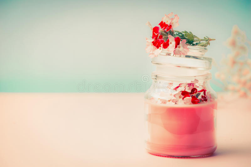 Pink cream in glass jar for skin care with flowers Stands on the table at turquoise background, front view. Beauty, cosmetic, spa royalty free stock photo