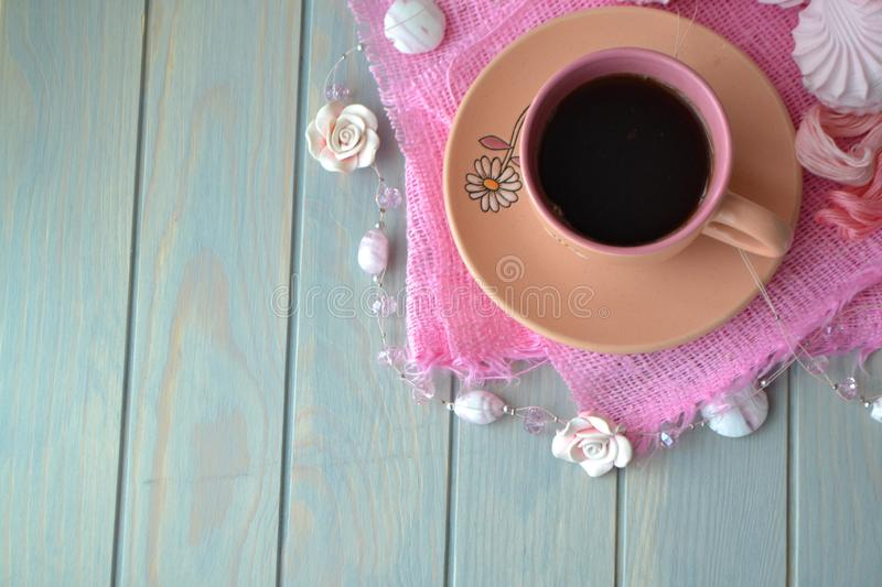 Pink cup of coffee on light teal wooden table. Top view, empty place, copy space. Vintage card concept stock image