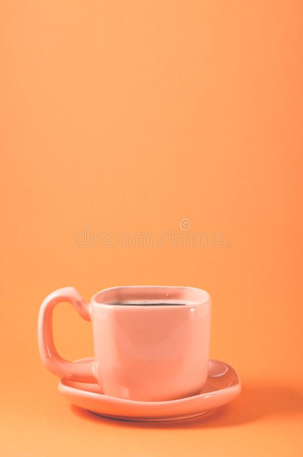 Pink cup with a saucer on a orange background/pink cup of coffee on a orange background, close up. Full black view top energy hot drink breakfast closeup royalty free stock image
