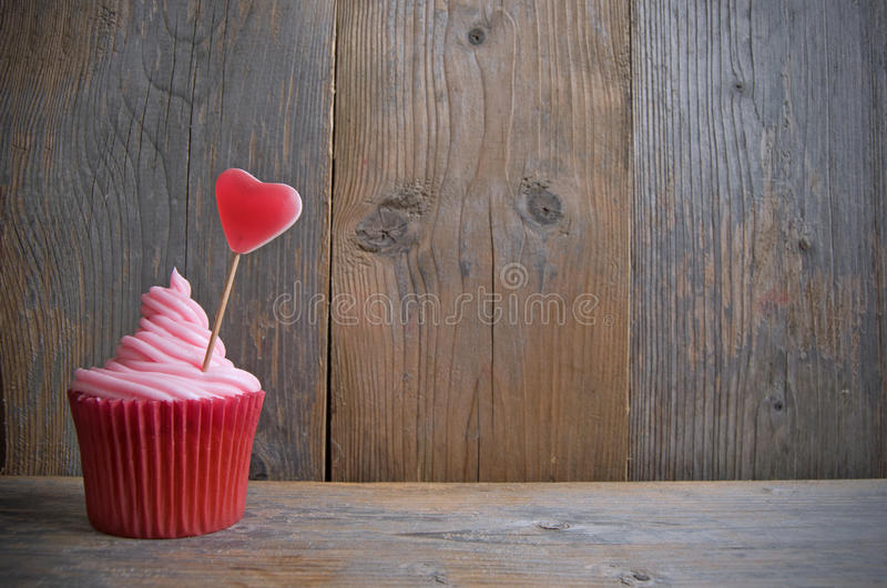 Pink cupcake with candy heart stock photo