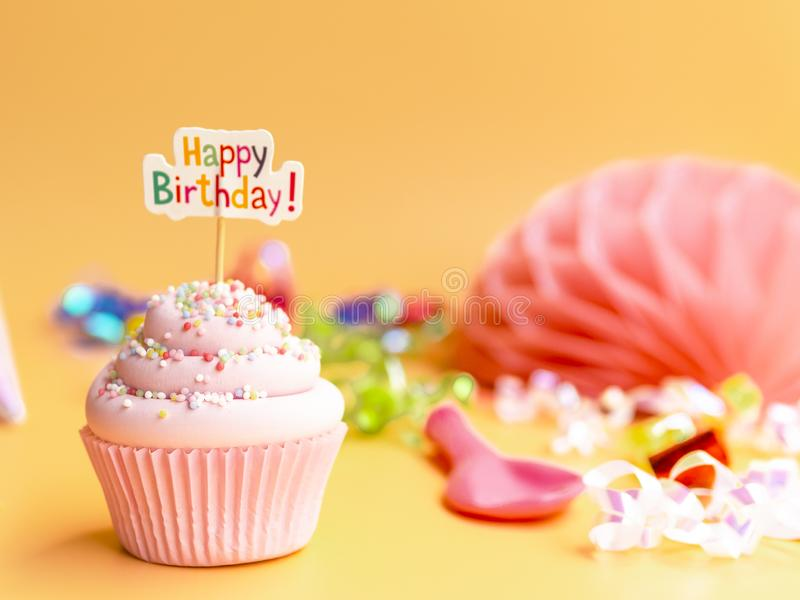 Pink cupcake with Happy Birthday text on beige background stock photos