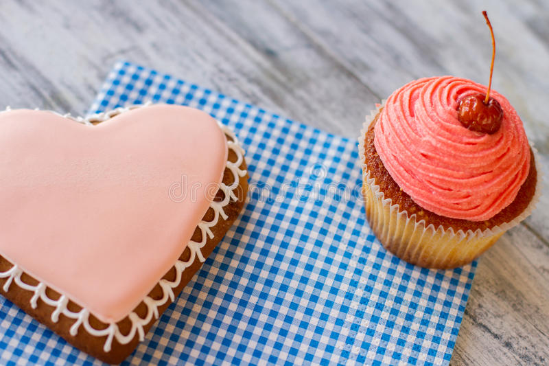 Pink cupcake and heart cookie. Desserts on blue napkin. Gray wooden table with sweets. Get imbued with feelings royalty free stock photos