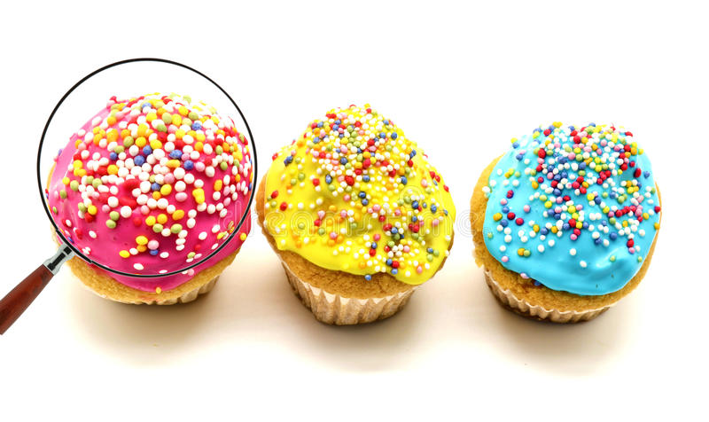 Pink cupcake view through magnifying glass royalty free stock photo