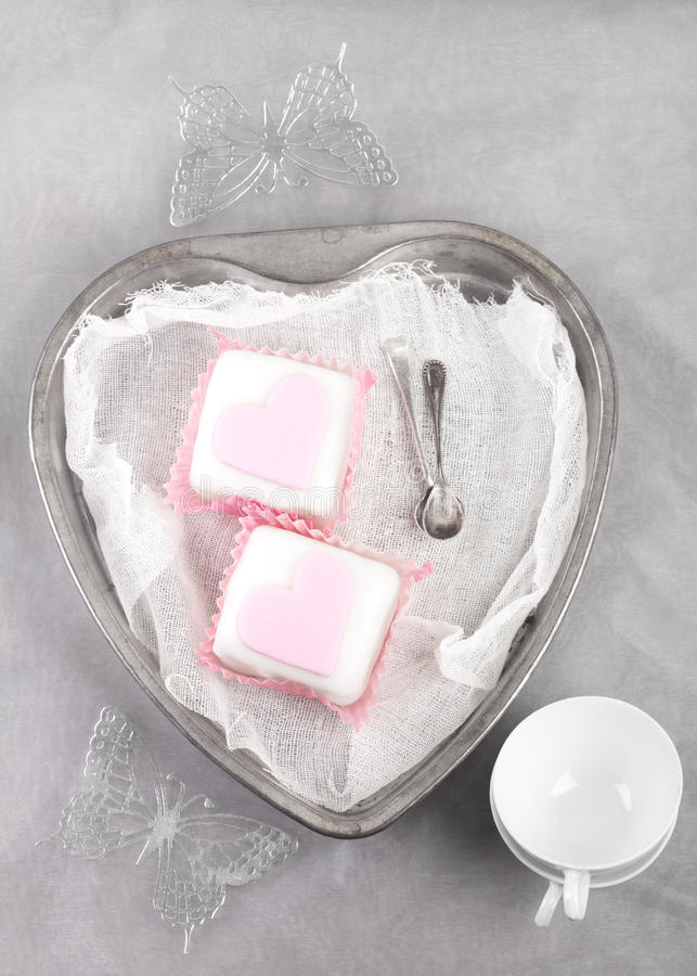 Download Pink Cupcakes In Heart Shaped Tin With Spoons Stock Photo - Image: 18057584