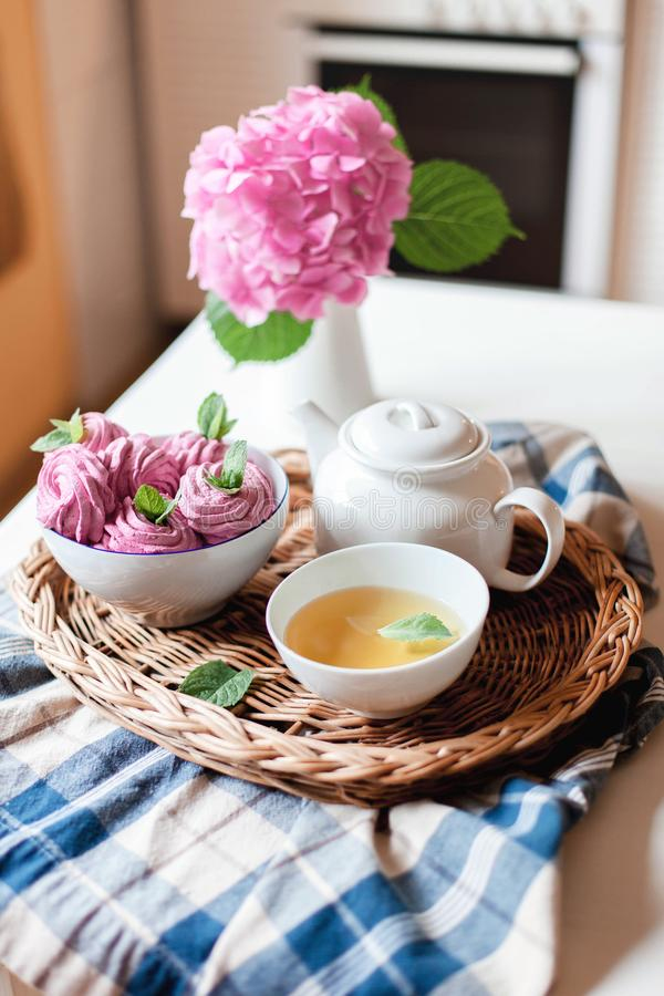 Pink cupcakes, mug of green mint tea, white teapot and hydrangea flowers on kitchen table. royalty free stock photo