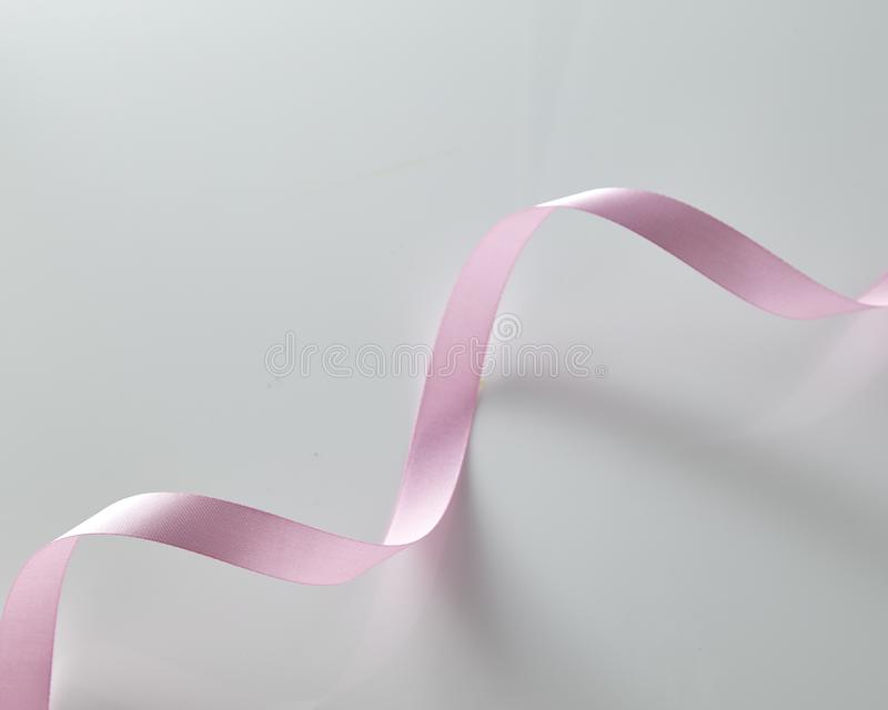 Pink curly ribbon on white stock photo