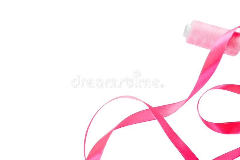 Pink curly satin ribbon and a spool of pink thread on a white background. Horizontal banner, on the left side a satin ribbon and royalty free stock image