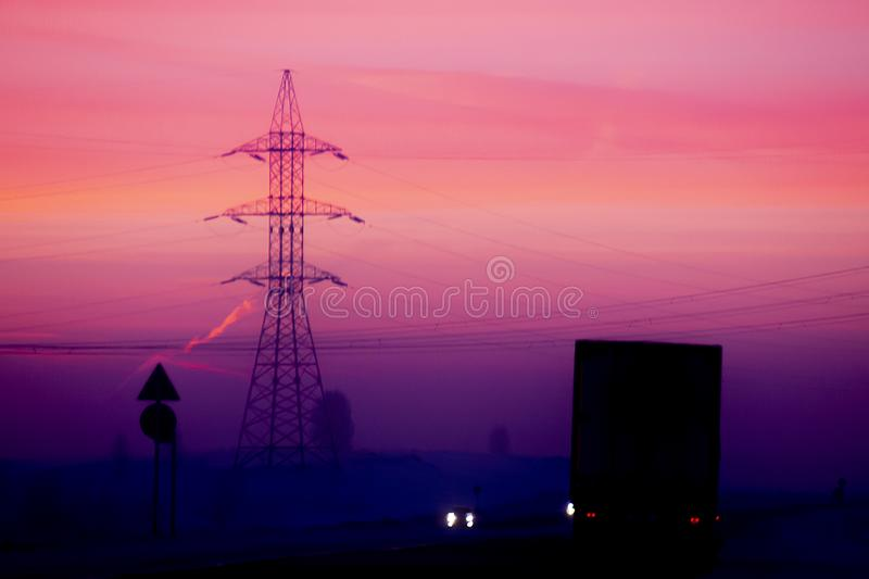 Pink dawn sky. Dark silhouettes of cars on the highway. stock photos