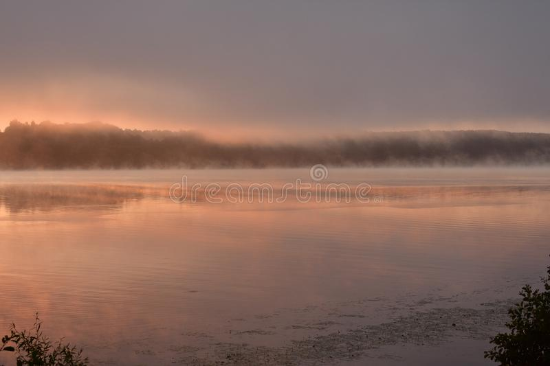 Pink dawn sunrise over the misty river, a solemn moment on the bright royalty free stock photos