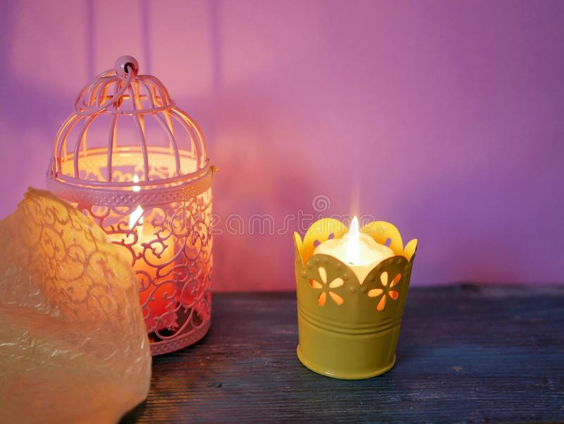 Pink decorative lantern with a burning candle, a burning candle in a yellow candlestick. On a blue wooden table royalty free stock photo