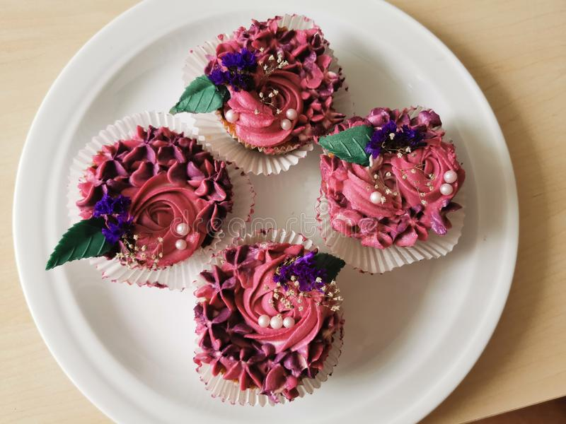 Pink Design Cupcakes in Macro. Pink, design, cupcakes, macro, sweet, delicious, flower, flowers, plate, white, paper royalty free stock photo