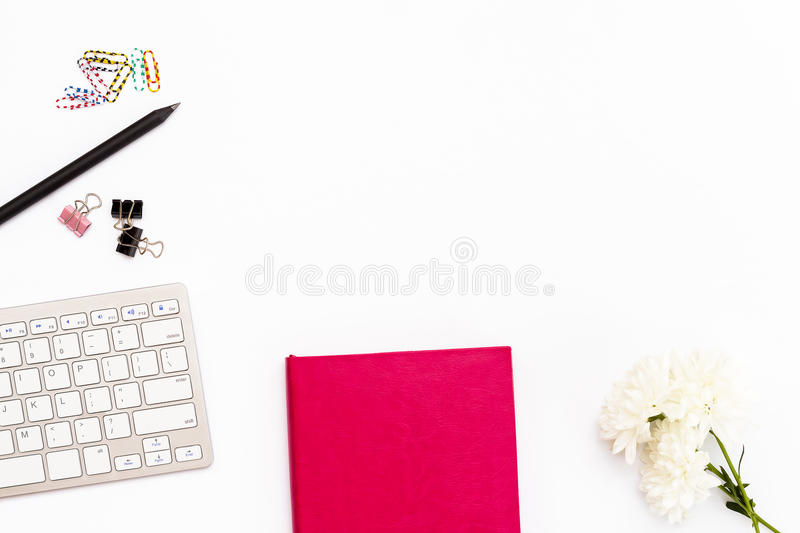 Pink diary and keyboard on a white background. Minimal feminine business concept. stock photography