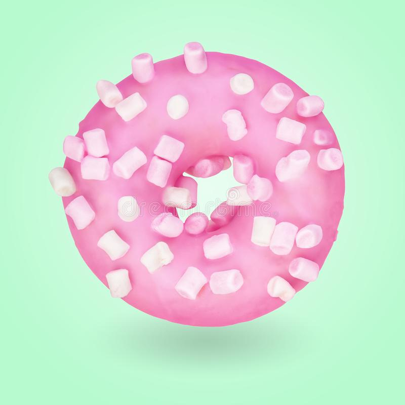 Pink donut on green backdround. Pink donut with marshmallow sprinkles on green background royalty free stock photo
