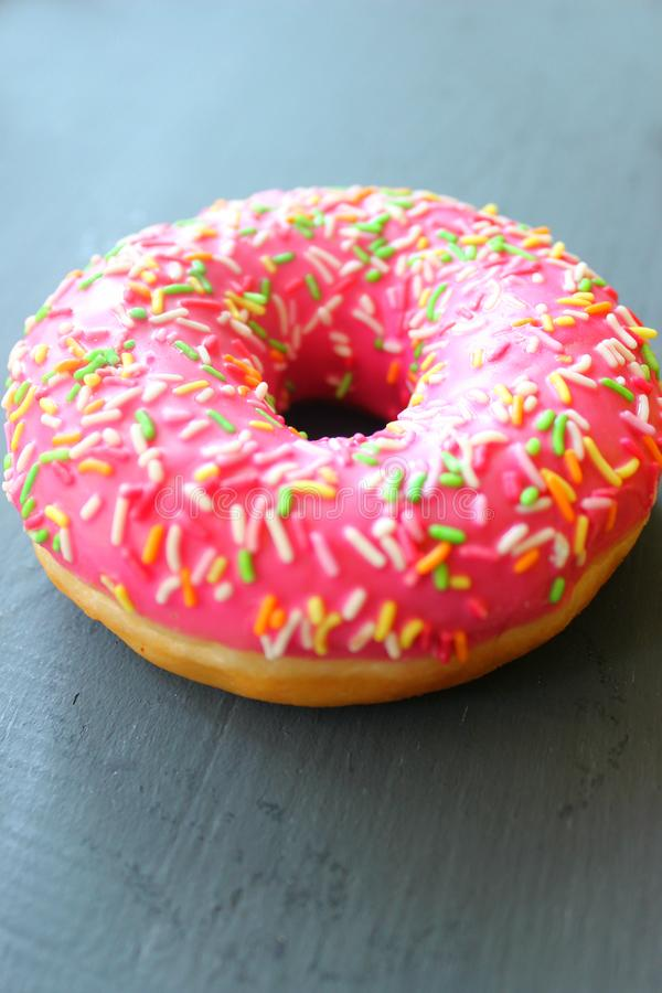 Pink doughnut with sprinkles on black background stock image