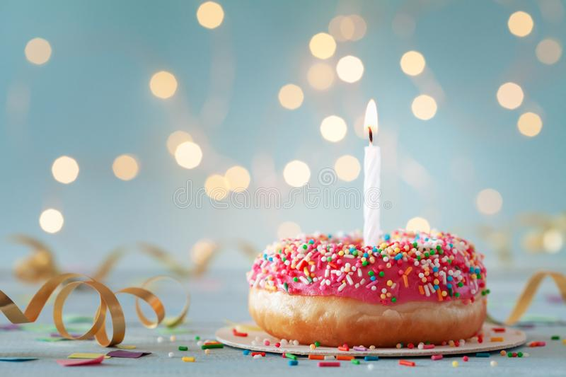 Pink donut and one burning candle against bokeh light background. Happy birthday concept.  stock photography