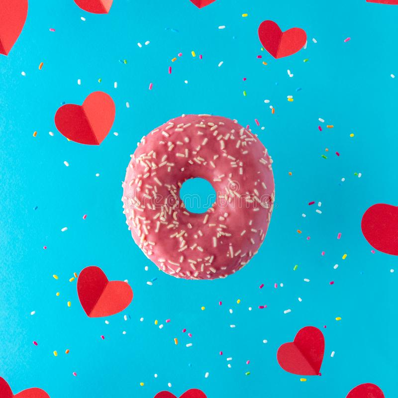 Pink donut with red paper hearts on a bright blue background. Minimal love concept stock image