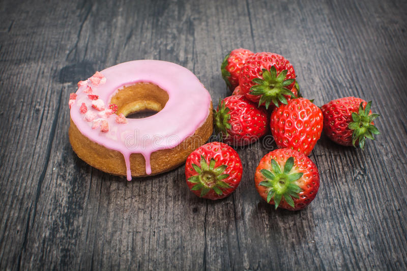 Pink donut and strawberry on the wooden desk stock photography