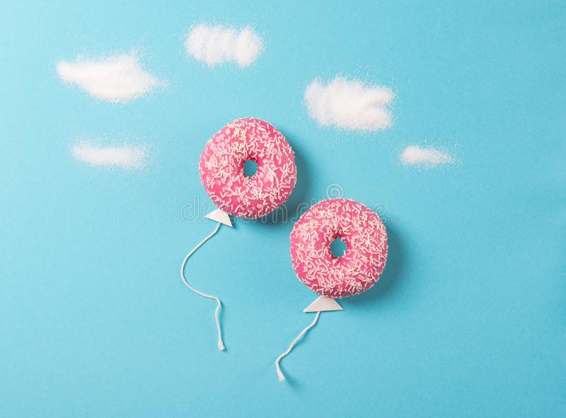 Pink donuts on blue background, creative food minimalism, donut in a shape of balloon in the sky with clouds made of sugar, top royalty free stock images