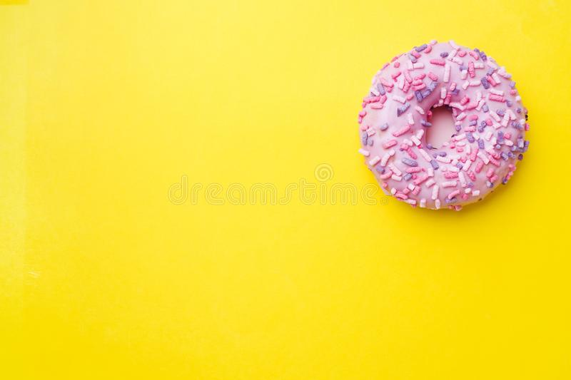 Pink doughnut on a yellow background. Top view Flat lay.  royalty free stock images
