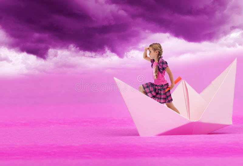 Pink dreams. Little girl sailing on paper boat under purple sky
