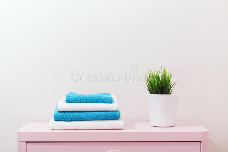On a pink dresser there is a pile of towels and a home plant sta. Nds stock photos