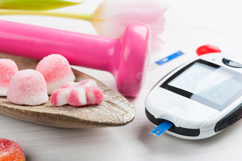Pink dumbbell, sweets and glucose meter. Concept for diabetes, lifestyle and healthy life royalty free stock photo