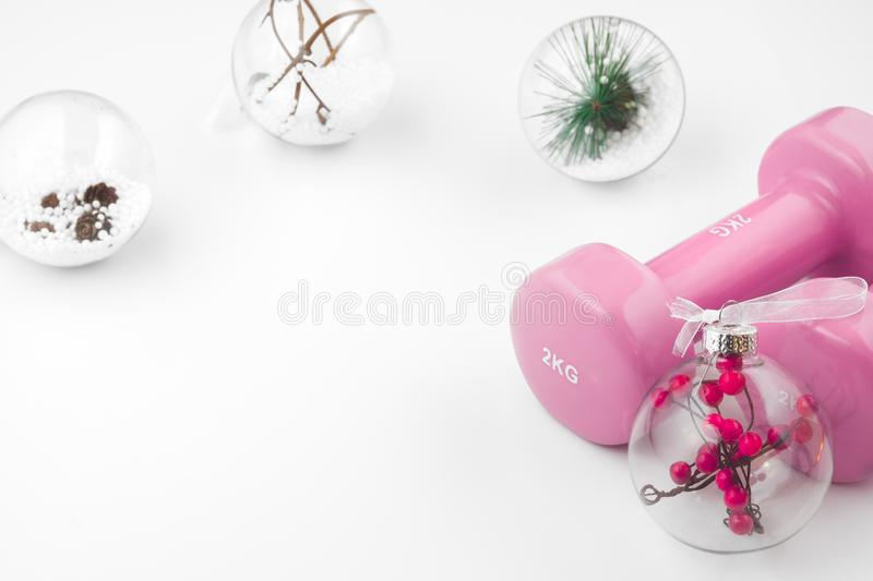 Pink Dumbbells and Christmas ornaments decoration on white background. Fitness Workout Chirstmas background concept. royalty free stock photos