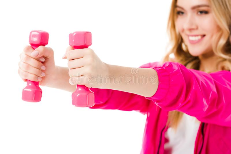 Pink dumbbells in hands of young girl royalty free stock images