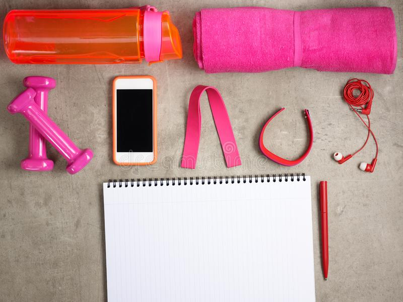Pink dumbbells, smartphone and opened notebook with pen. Closeup on pink dumbbells, towel, bottle of water, headphones, fitness tracker, elastic band, smartphone royalty free stock images